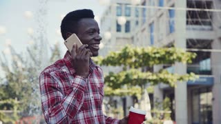 Young Afro american man talking by smartphone, smiling as he listens to the conversation on an urban street