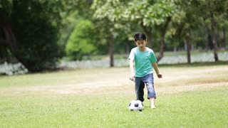 Young asian boy playing soccer in a park, Bangkok Thailand