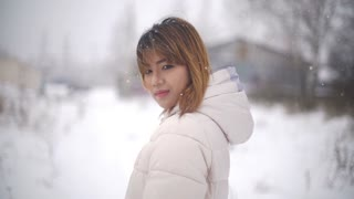 Young Asian Woman during snowfall. Slowmotion