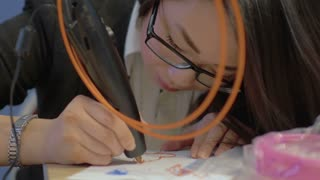 Young asian woman is drawing a heart shape on a paper sheet using 3D printing pen.