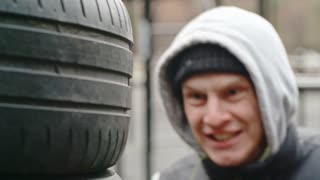 Young athlete in boxing gloves punching old tires with force and fierce expression on his face