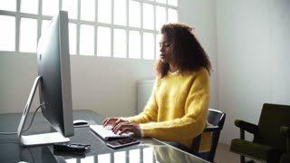 Young attractive black girl working on her project on computer, takes a break and dreamily looks at window, then works again in industrial office