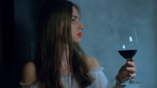 Young attractive Caucasian female holding a glass of red wine. 4K cinemagraph - motion photo seamless loop. Shot with Blackmagic URSA Mini