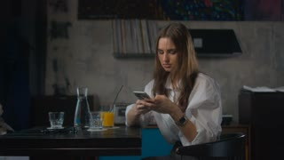 Young attractive Caucasian female using her phone in retro styled cafe. 4K cinemagraph - motion photo seamless loop. Shot with Blackmagic URSA Mini