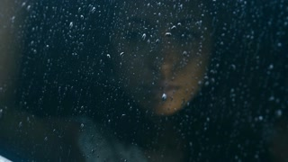 Young attractive Caucasian woman sitting in the car on a rainy day, drops fall on the window. HD cinemagraph, motion photo - seamless loop. Canon RAW edited footage.