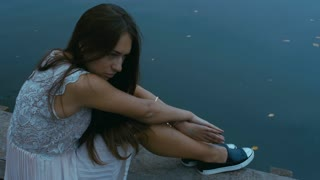 Young attractive Caucasian woman sitting on an old pier. HD cinemagraph, motion photo - seamless loop. Canon RAW edited footage.