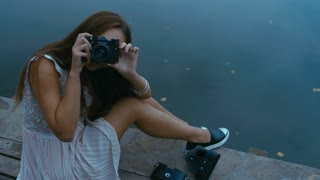 Young attractive Caucasian woman taking pictures with vintage camera on an old pier. HD cinemagraph - motion photo seamless loop. Canon RAW edited footage.