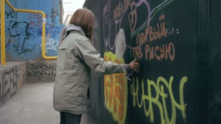 Young attractive female painting graffiti on the wall