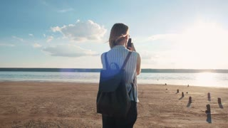 Young attractive woman taking photo of beautiful sunset on the beach, slow motion