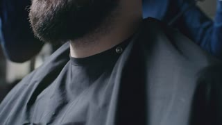 Young bearded man sitting in barbershop and smiling while hairstylist drying his hair