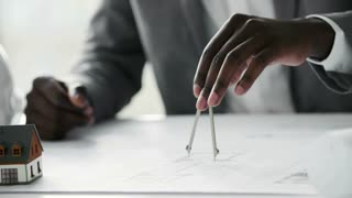 Young black architect working on construction blueprint in white office, he draws with a divider and ruler. Slow motion