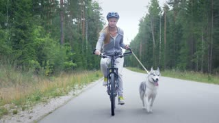 Young blond girl cycling with her dog on the road