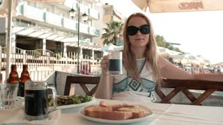 Young blond woman having a meal in an outdoor restaurant during summer holidays