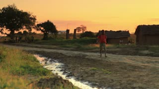 Young Boy Walking Up Dirt Road at Sunset