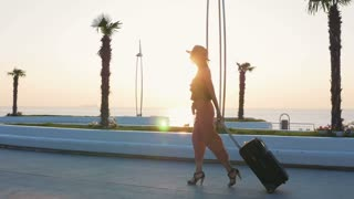 Young business lady walking with suitcase at the seafront, slow motion