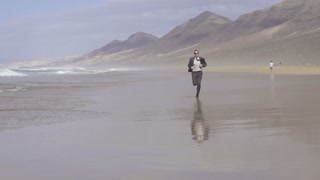 Young businessman jogging on the beach, slow motion shot at 60fps