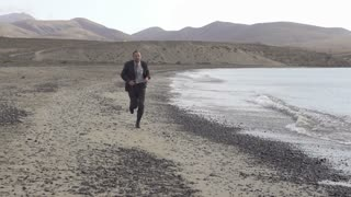 Young businessman jogging on the seashore with cellphone, slow motion