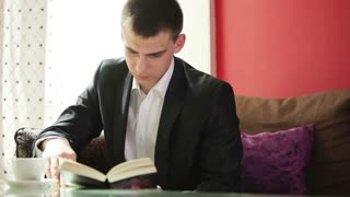 Young businessman reading a book and laughing at camera