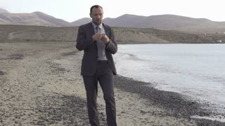 Young businessman standing on the seashore with cellphone, slow motion shot
