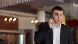 Young businessman talking on the phone and smiling at camera