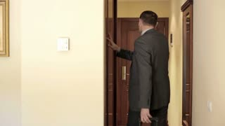 Young businessman with case leaving the hotel room