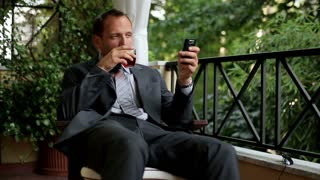Young businessman with cellphone after hard work drinking whiskey on his balcony
