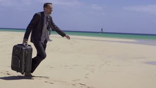 Young businessman with suitcase on the beach, slow motion shot at 240fps
