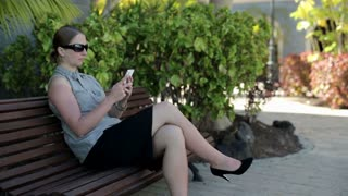 Young businesswoman in tourist resort with cellphone on the bench