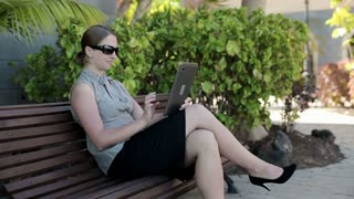 Young businesswoman in tourist resort working with tablet computer on the bench