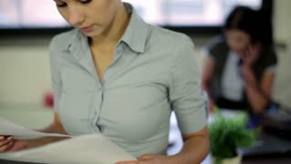 Young businesswoman reading documents in office
