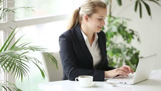 Young businesswoman sitting at office table talking on mobile phone and looking at camera with smile