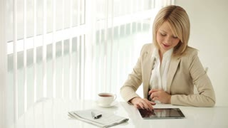 Young businesswoman sitting at table using touchpad drinking coffee and smiling