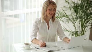 Young businesswoman sitting at table with newspaper and using laptop