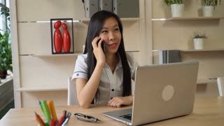 Young businesswoman sitting in the owen office talk with customer or partner. Secretary wearing in formal white shirt with short sleeves. Vietnamese girl looking to the camera and smiling