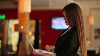 Young businesswoman standing at cafe and typing on laptop