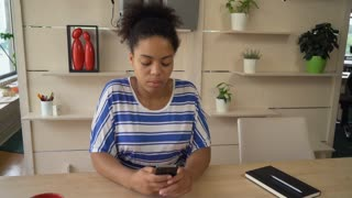 Young businesswoman texting sms on mobile phone. Happy smiling female send message on cell. Smiling black model wearing in casual clothes working in modern creative office startup or big company