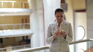 Young businesswoman with smartphone in the office hall, steadycam shot