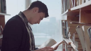 Young caucasian man standing at bookshelf in library, looking through book flipping and turning pages, searching for information with focused look