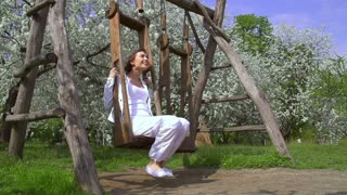 Young cheerful woman is having fun on the swings in the spring park. Slow motion. Filmed at 250 fps