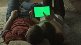 Young Couple are Laying on the floor and Using Tablet PC with Green Screen at Home at Evening Time. Casual Lifestyle.
