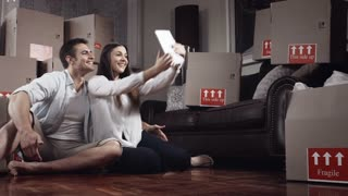 Young couple doing selfie or self portrait in for memories in there new apartment while moving in.