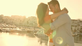 Young couple hugging by marina in sunset.