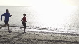 Young couple jogging on the beach, slow motion shot at 240fps