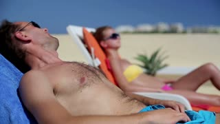 Young couple lying on sunbed and applying sun cream