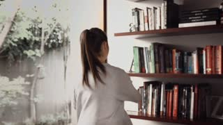 Young couple packing a book shelf in there new apartment.