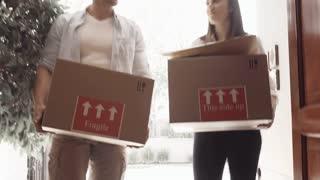 Young couple picking up moving boxes and walking through their door of new apartment while moving in.