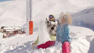 Young couple playing in the snow at a ski resort
