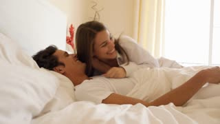 Young couple playing on bed