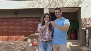 Young couple portrait smile with happiness with new house keys for their new home.