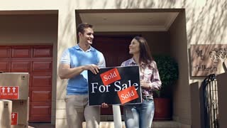 Young couple portrait that are very happy with there new house and holding there sold for sale board while moving into a new house.